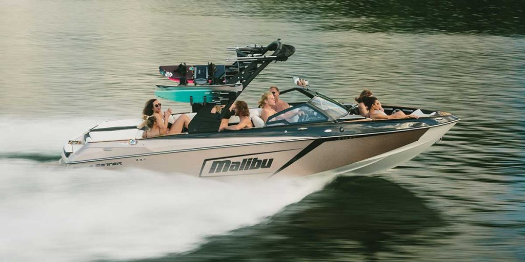 a few wakeboarders sit aboard a malibu 23LSV as it speeds across the lake water.