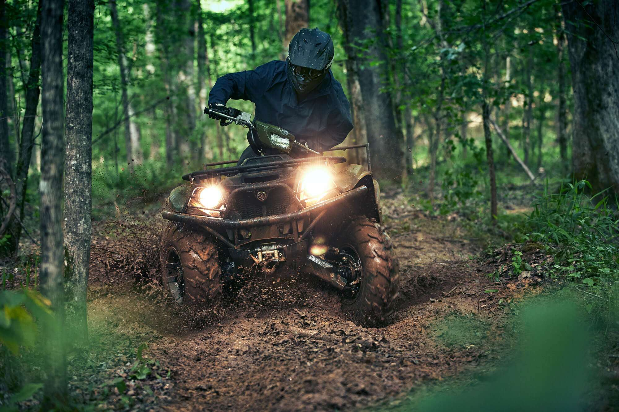 A man driving an ATV in the woods