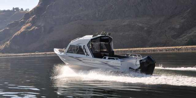 a thunderjet alexis crossover fishing and utility boat motoring across clear waters.
