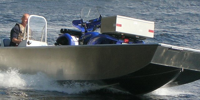 a  driver expertly handles a Stanley Predator aluminum boat across the lake water.