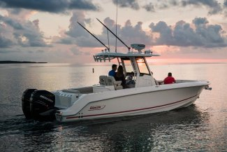 A boston whaler 280 Outrage center console fishing boat in with an older couple looking at a Gordon Bay sunset.