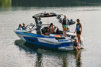 a malibu boat hosting a few friends having a good time on the water.