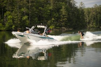 a happy wakeboarder carves behind an Axis A24 2020