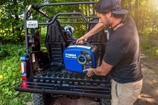 a young man loads his Yamaha 20IST2 inverter onto the back of his ATV.